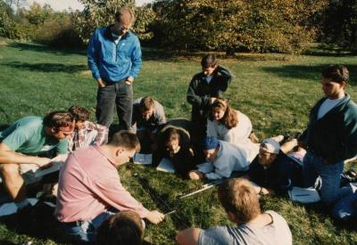 Pat Kelsey and class studying soil, seated on grass in an open field