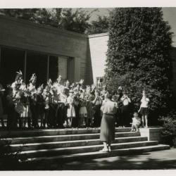 May Watts leading group of children wearing feather headbands in musical performance on steps outside of Thornhill