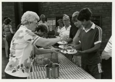 Fish Boil: Volunteer, Marge Clink, serving food behind table to visitors outside Visitor Center