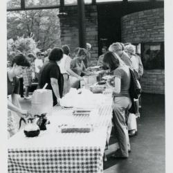 Fish Boil: Susan Klatt and others serving food and beverages behind tables outside Visitor Center