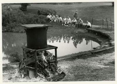 Fish Boil: kettle on flame, people seated by Meadow Lake in background