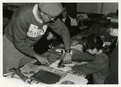 Family Fair: man assists child in nature printing
