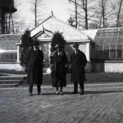Two men and one woman at Morton residence greenhouse with water tank in background