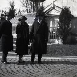 Two men and one woman in front of Morton residence greenhouse