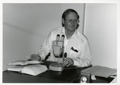 Ross Clark working with microscope at desk