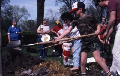 Crowd watching woman and young boy  with shovels planting tree at Arborfest
