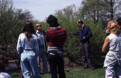 Tom Green talking to crowd in front of shrubs during Arborfest