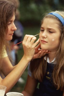 Woman painting girl's face on Arbor Day