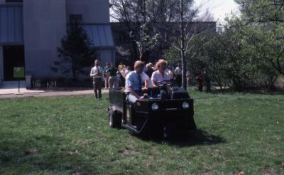 Dr. Tom Green and Karla Patterson in cart leading line of people across lawn near Research building for tree planting at Arborfest