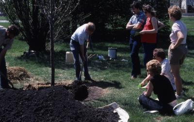 Dr. Tom Green with shovel planting tree at Arborfest with visitors