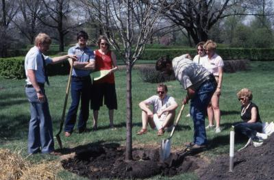 Tom Green with shovel watching tree planting