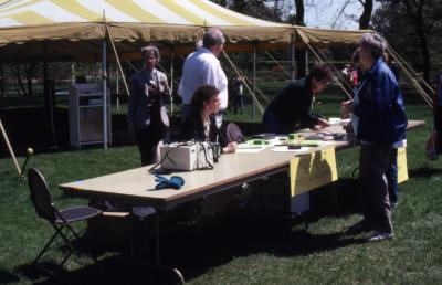 Staff at ticket and information table in front of tent during Arborfest