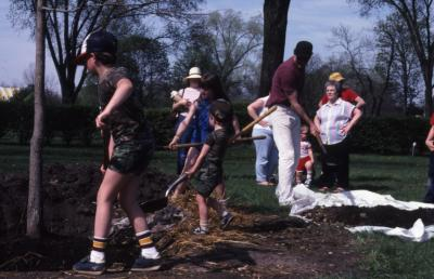 Three children with shovels planting tree at Arborfest
