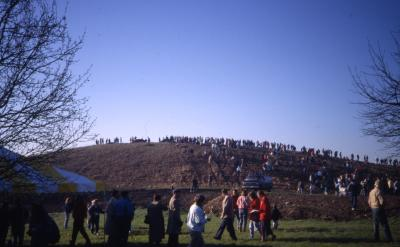 Crowd walking up berm and lined up on top of berm on Earth Day