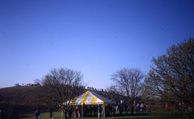 View of crowd in yellow tent near berm on Earth Day