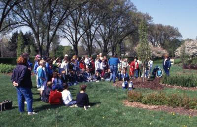Deb Seymour assisting crowd, mainly children, with shovels at Arbor Day tree planting near Hedge Garden