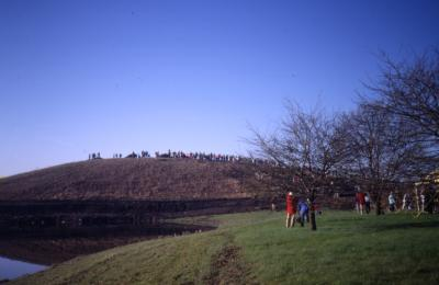 View from alongside Crabapple Lake toward berm with crowd lined up on top of berm on Earth Day