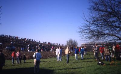 Crowd on and walking toward berm with building at right in distance on Earth Day
