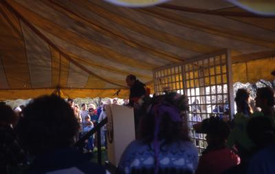Dr. Marion Hall speaking to crowd in tent on Earth Day