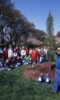 Deb Seymour near Arbor Day planted tree with crowd, mainly children, gathered around near Hedge Garden