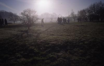 Morning sun in mist over crowd gathering for Earth Day tree planting