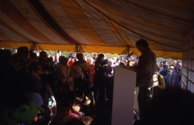 Joe Larkin in tent speaking to large crowd on Earth Day