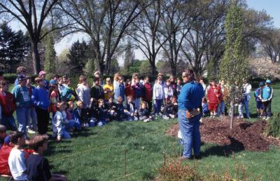 Deb Seymour speaking to crowd, mainly children, at Arbor Day tree planting near Hedge Garden