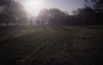Sun in morning mist with crowd gathering for Earth Day tree planting