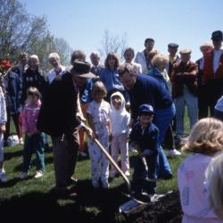 Crowd with two adults, one with hat, and three children planting tree on Arbor Day