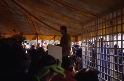 Joe Larkin speaking to crowd in tent on Earth Day