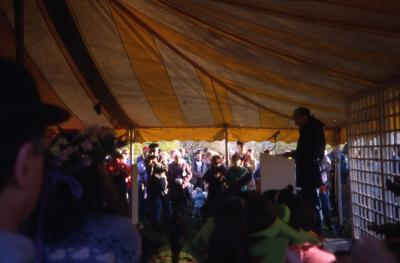 Dr. Marion Hall in tent speaking to crowd on Earth Day