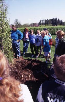 Group with Deb Seymour near Hedge Garden shoveling soil at Arbor Day tree planting