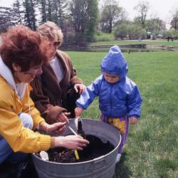 Susan Klatt helping toddler plant tree seedling during Arbor Week celebration