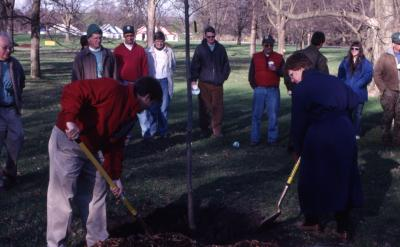 Kris Bachtell and Patti Jelen shoveling soil over newly planted tree at Arbor Day employee tree planting