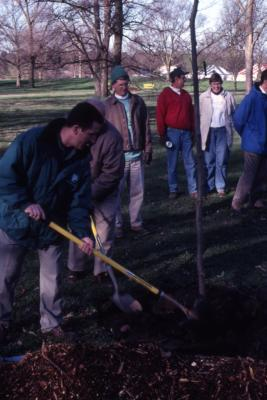 Scott Moberg shoveling soil over newly planted tree at Arbor Day employee tree planting