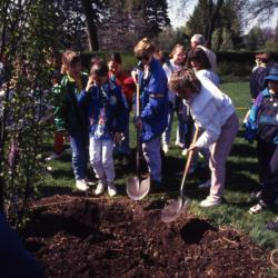 Adults and children with shovels at Arbor Day tree planting