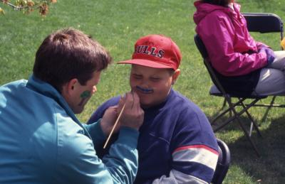 Kris Bachtell painting mustache on boy during Arbor week