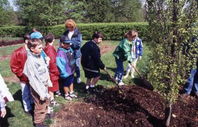 Group of children watch as boy and girl shovel soil at Arbor Day tree planting