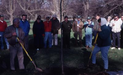 George Ware and other employee shovel soil over newly planted tree at Arbor Day employee tree planting