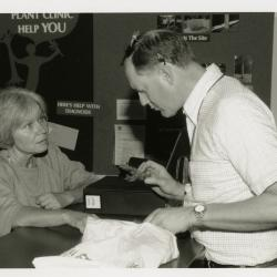 Ed Hedborn examining plant material with woman at Plant Clinic desk