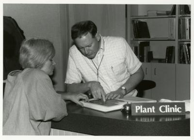 Ed Hedborn reviewing images of plants in book with woman at Plant Clinic desk