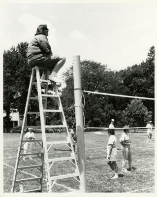 Deb Seymour, referee, seated on ladder looking over employee summer picnic volleyball game near the Research Building