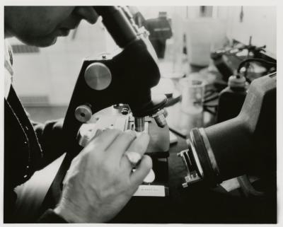 Closeup of man using microsope in laboratory