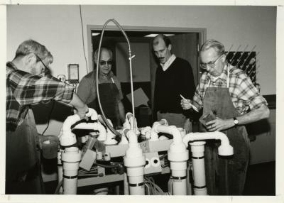 Research crew operating a hydropneumatic elutriation root washing system in laboratory