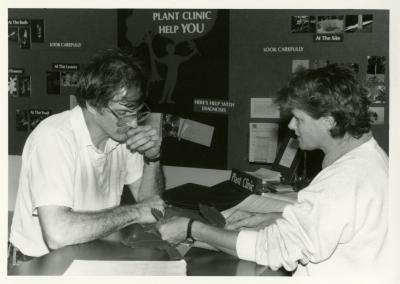 Doris Taylor examining plant leaves with man at Plant Clinic desk