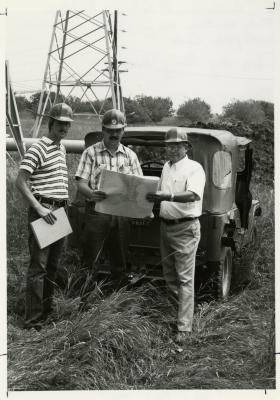 Rick Hootman (left), Pat Kelsey, and George Ware (right) in hard hats studying contour maps for future site of Crabapple Lake