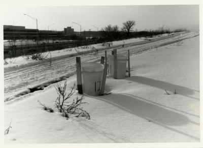 Salt study, plastic buckets on snow-covered berm along freeway
