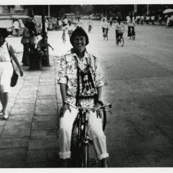 Carol Doty riding bicycle on street in China