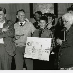 Jim Fuqua Retirement Party in Founders Room - Tony Tyznik (2nd from left) including grandson and Fran Fuqua with poster