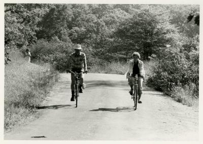 Members' bike ride, Kitty Kohout at edge of woods